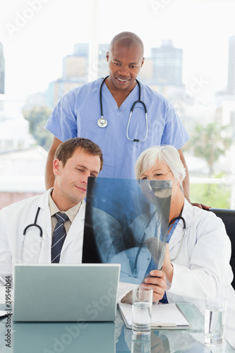 Mature doctor explains an x-ray to colleagues