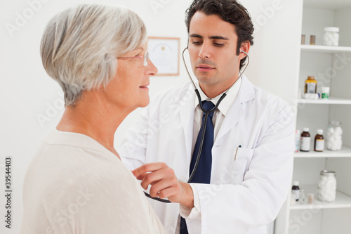 Doctor taking mature patients heart beat
