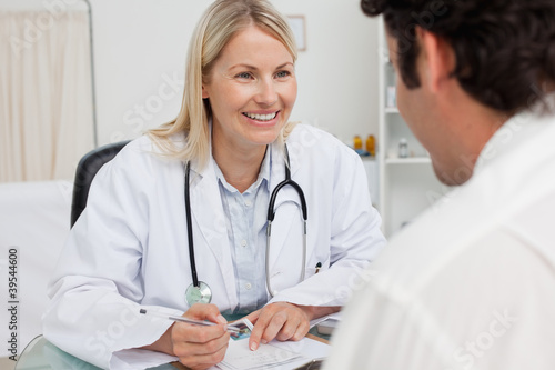 Smiling doctor taking notes while listening to patient