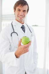 A surgeon is holding a green apple