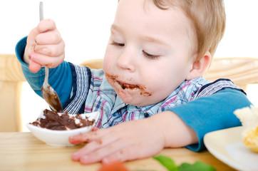 kleiner Junge isst Nougatcreme mit Löffel