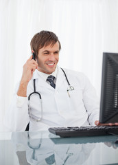 Smiling doctor looking at his computer while using his mobile phone