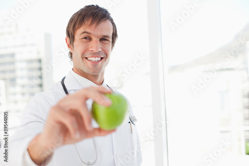 Smiling surgeon is holding a green apple