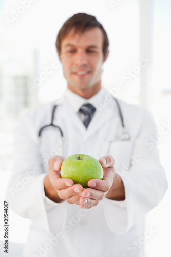 Delicious green apple in the hands of a smiling surgeon in a bright room