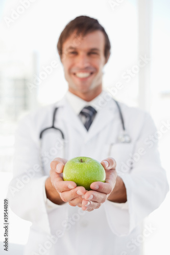 A happy doctor is holding a green apple