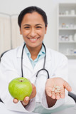 Delicious green apple and vitamins being held by a doctor
