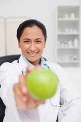Smiling practitioner holding a green apple