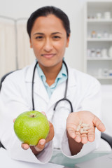 Relaxed doctor holding a green apple and vitamins
