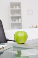 Delicious green apple placed on a laptop