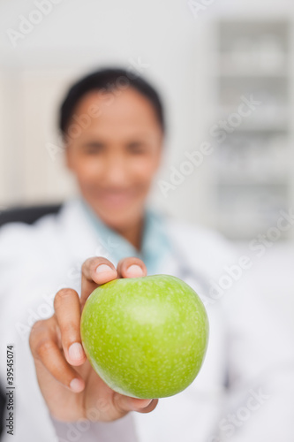 Big green apple being held by a doctor