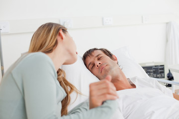Patient sleeping in a hospital bed while his wife is looking at him