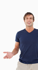 Smiling man looking away while standing up with his hand outstretched