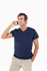 Smiling man standing upright while talking on the phone
