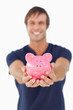 Piggy bank held by a young man