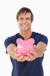 Smiling man holding a pink piggy bank