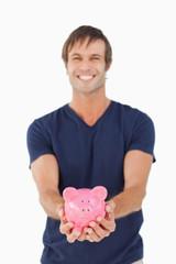 Smiling man holding a piggy bank