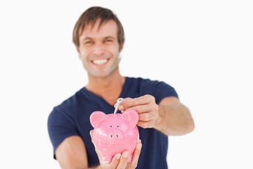 Piggy bank held by a man and receiving notes