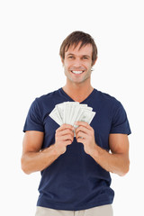 Fan of bank notes held by a smiling man