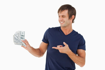 Young man proudly holding a fan of notes while pointing at it