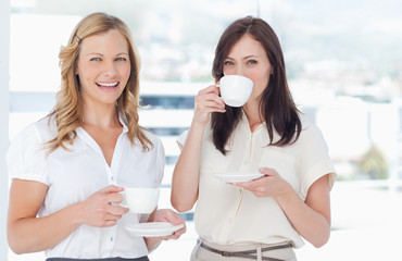 Woman smiling as she stands next to her friend who is drinking tea