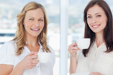 Two friends smiling as they look ahead while drinking tea