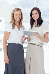 Woman smiling while holding a tablet and standing next to her friend