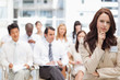 Businesswoman looking ahead as she stands in front of her colleagues