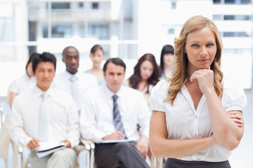 Businesswoman resting her chin on her hand while standing in front of her colleagues