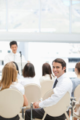 Happy businessman looking behind him during a presentation