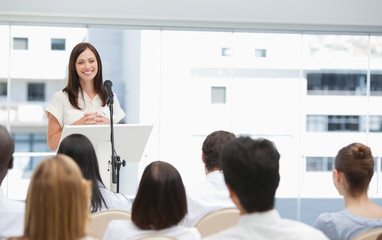 Businesswoman giving a speech while she is being watched