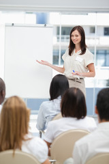 Businesswoman smiling while using a chart during a presentation