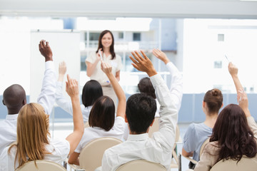 Audience raising their hands while watching a businesswoman