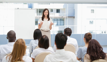 Businesswoman gesturing towards an audience during a presentation