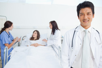 Doctor looking ahead while his colleagues treat a patient