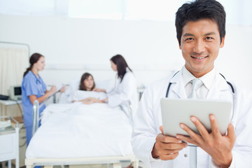 Doctor looking ahead while holding a tablet as his colleagues treat a patient