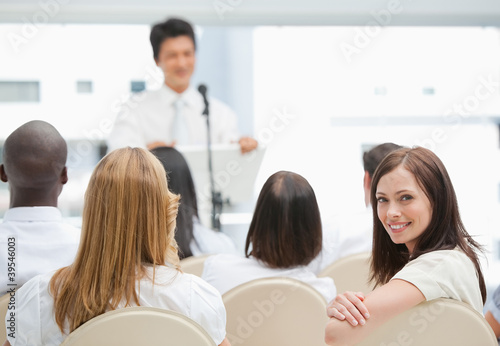 Happy businesswoman looking behind her during a presentation