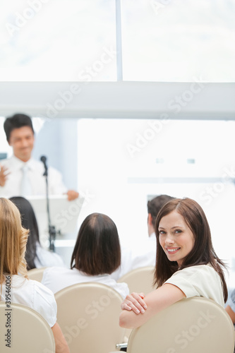 Close-up of a happy businesswoman looking behind her during a presentation