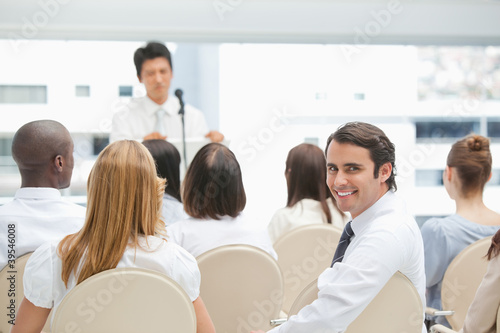 Businessman smiling as he looks behind him during a speech