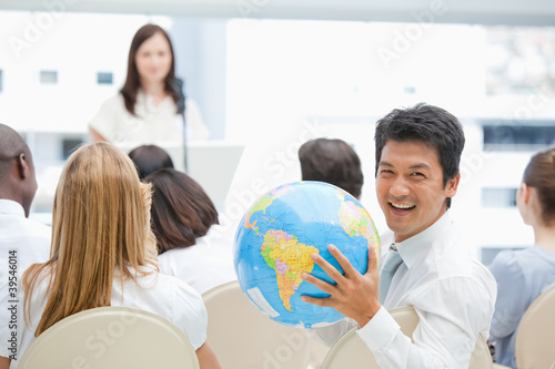 Man laughing while holding a globe during a speech
