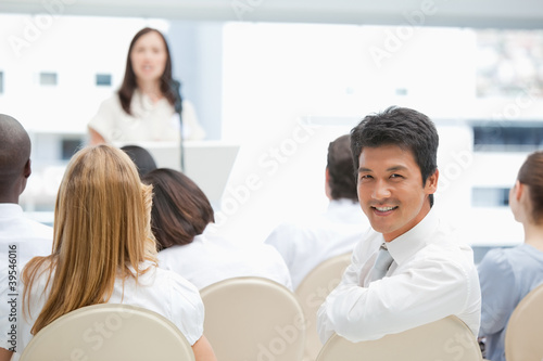 Smiling businessman looking behind him during a speech