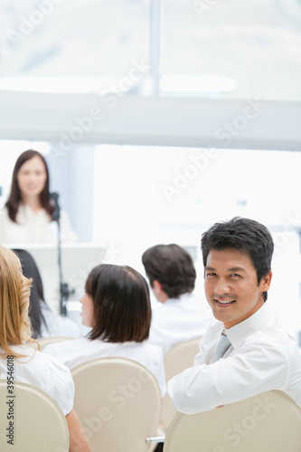 Businessman smiling while looking behind him during a speech