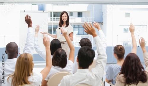 Audience have their arms raised as they watch a businesswoman