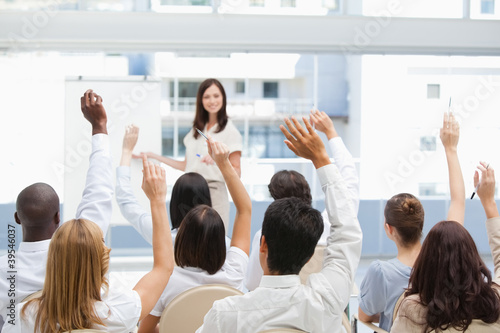Audience raising their arms while watching a businesswoman