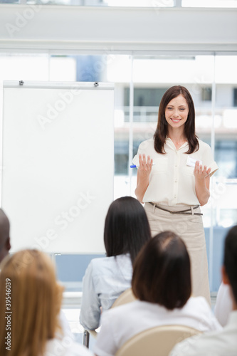 Woman smiling while gesturing towards an audience