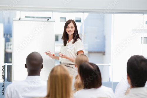 Woman holding a marker as she looks at the audience