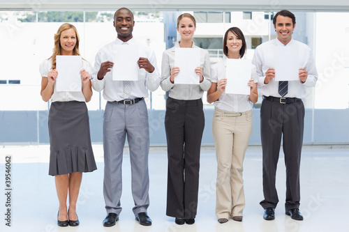 Business team holding white sheets in front of them