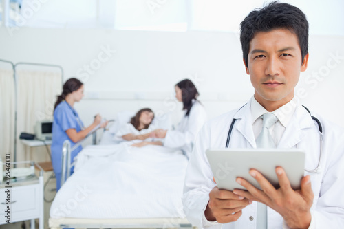 Serious doctor looking ahead while holding a tablet as his colleagues treat a patient