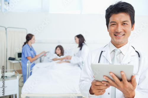 Doctor smiling while holding a tablet as he stands in front of his colleagues