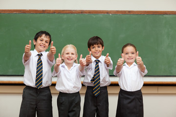 Smiling children in school uniforms giving thumbs up