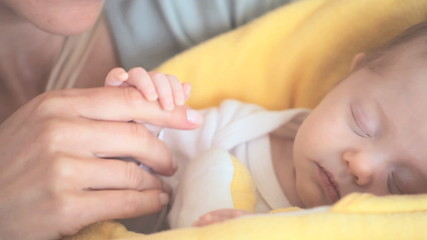 Woman holding her baby's hand